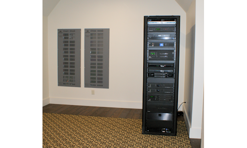 A/V & network equipment rack with lighting control panels shown in wall